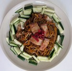 pork belly on Hokkien fried noodles garnished with cucumber